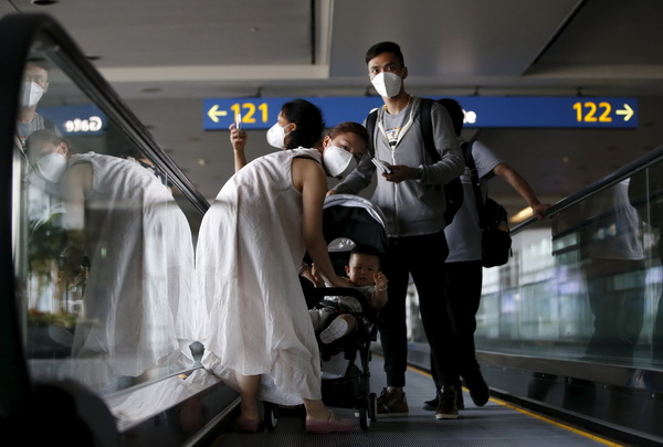 Passengers wearing masks to prevent contracting Middle East Respiratory Syndrome (MERS) ride on a travelator upon arrival at Incheon International Airport in Incheon, South Korea, June 2, 2015. South Korea on Tuesday reported its first two deaths from an outbreak of MERS that has infected 25 people in two weeks, as public alarm grew and officials scrambled to contain the outbreak. REUTERS/Kim Hong-Ji      TPX IMAGES OF THE DAY