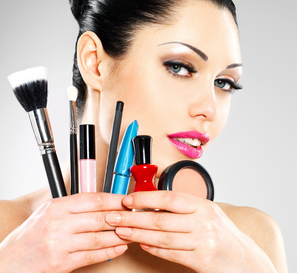 Beautiful woman with makeup brushes near her face. Pretty girl p