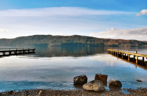 Picturesque lake with two wooden jetties and backed by low mountains in Windermere, English Lake District