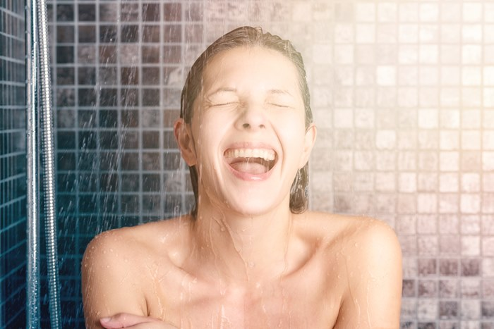 Close up Happy Bare Young Woman Taking Shower at the Bathroom with Mouth Open and Eyes Closed.