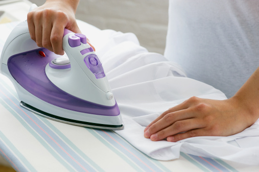 Woman ironing blouse on ironing board, close-up
