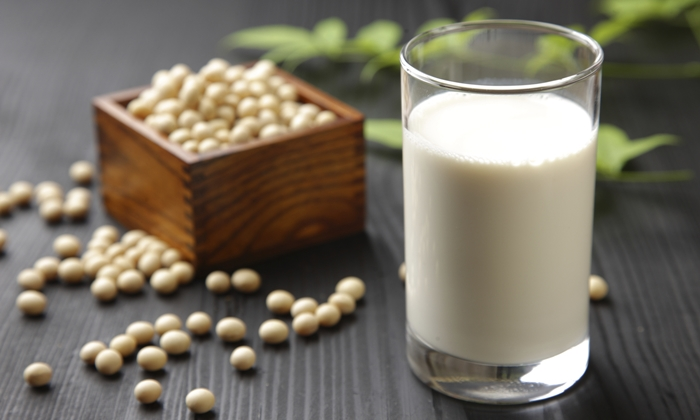 close up shot of a glass of soymilk and soybeans