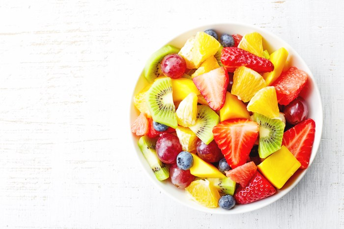 Bowl of healthy fresh fruit salad on wooden background. Top view.