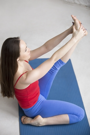 Beautiful young woman in bright colorful sportswear working out indoors in loft interior on blue mat. Girl sitting in Heron pose, Krounchasana, for legs strength and flexibility. Full length