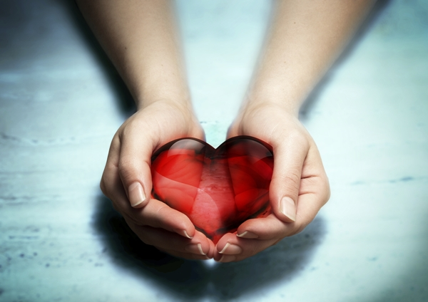 two hands holding red crystal heart