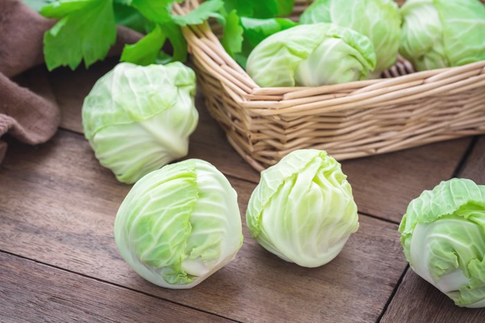 Cabbage on wooden table and basket