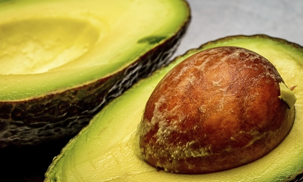 Cut open avocado in the fresh state, revealing the texture of a large single seed structure. This fruit is loaded with important nutrients to support health.