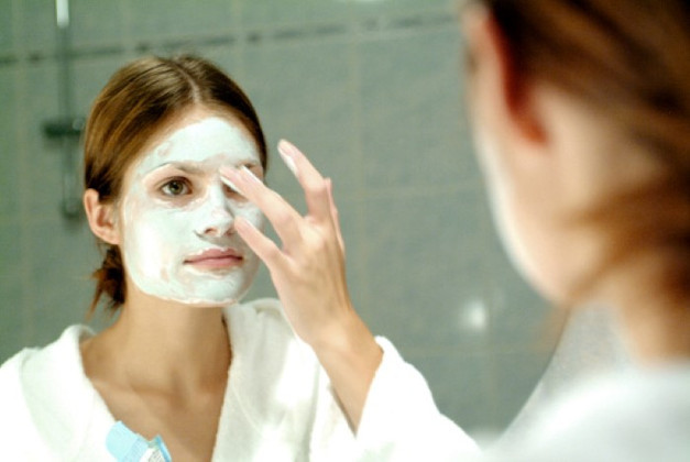 Close-up of a young woman applying a facial mask