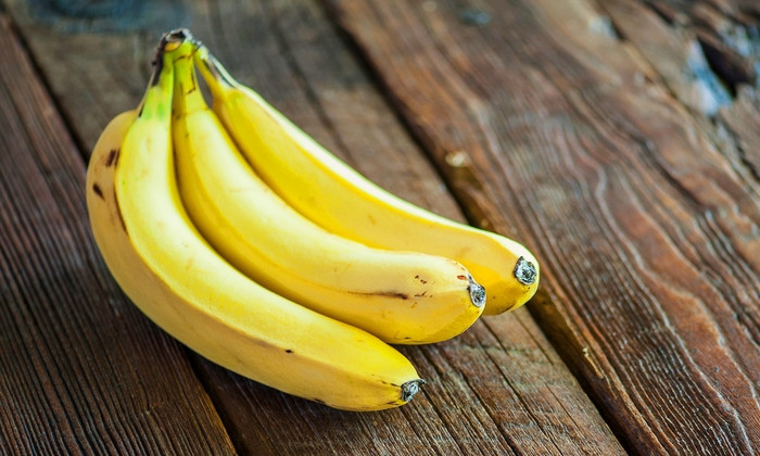 Close-up view of a bunch of ripe bananas on a rustic, wooden tabletop, shallow DOF
